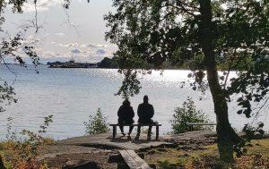 Kaksi ihmistä istuu rauhassa vierekkäin joen rannalla, valokuva.